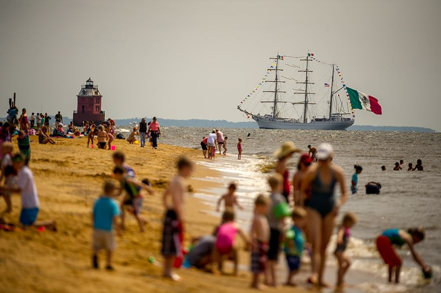 """Revelers line the beach at Sandy Point State Park in Annapolis, Md., on June 13, 2012, as tall ships pass under the Chesapeake Bay Bridge en route to the Inner Harbor in Baltimore for a bicentennial commemoration of the War of 1812. The week-long """"Star-Spangled Sailabration"""" includes free tours of the ships, waterside festivities, an air show featuring the Blue Angels and the world premiere of """"Overture for 2012,"""" composed by Philip Glass. (Andrew Harnik/The Washington Times)"""