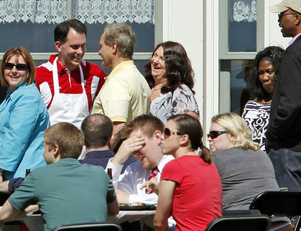 """**FILE** Wisconsin Gov. Scott Walker (standing, in red) and state Rep. Peter Barca (in yellow), Kenosha Democrat, talk June 12, 2012, during Walker's """"brat summit"""" at the executive residence in the Village of Maple Bluff, Wis. (Associated Press/Wisconsin State Journal)"""