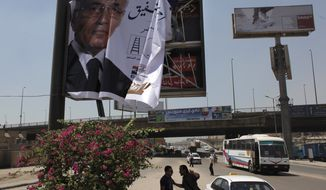 "A laborer installs an election poster for Egyptian presidential runoff candidate Ahmed Shafiq on the side of a highway in Cairo on Monday, June 11, 2012. The Arabic, partially shown, translates as ""Ahmed Shafiq, President for Egypt."" (AP Photo/Nasser Nasser)"