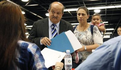 Jose Canales (left), accompanied by his wife, Magdel, and daughter Alexamarie, talks with a recruiter at a job fair in Anaheim, Calif., on Wednesday, June 13, 2012. (AP Photo/Jae C. Hong)