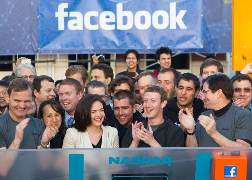 Mark Zuckerberg (center), Facebook founder, chairman and CEO, applauds at the opening bell of the Nasdaq stock market on May 18, 2012, from Facebook headquarters in Menlo Park, Calif. (Associated Press/Nasdaq via Facebook, Zef Nikolla)