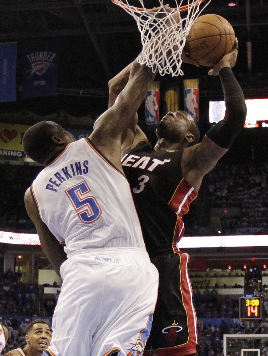 Miami Heat shooting guard Dwyane Wade shoots against Oklahoma City Thunder center Kendrick Perkins during the second half of Game 2 of the NBA finals Thursday, June 14, 2012, in Oklahoma City. (AP Photo/Jeff Roberson Pool)