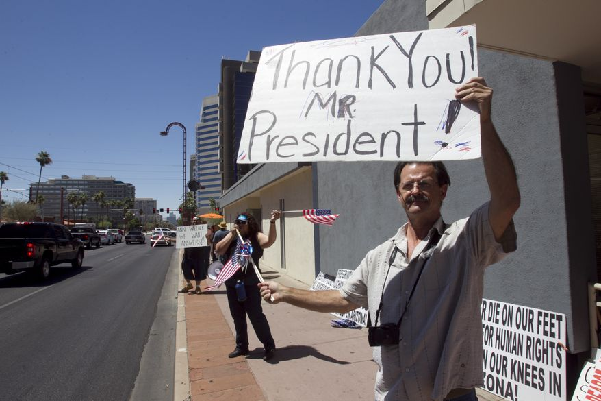 Nick Thomas, 53, of Phoenix holds a sign thanking President Obama at the Arizona Democratic Party in Phoenix on June 15, 2012, after the president announced the easing of enforcement of immigration laws, effective immediately. The new policy offers a chance for hundreds of thousands of younger illegal immigrants to stay in the U.S. and work. (Associated Press/The Arizona Republic)