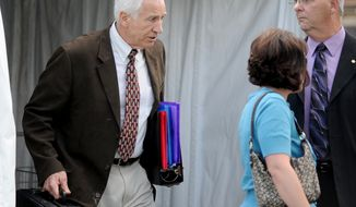 Jerry Sandusky, left, leaves the Centre County Courthouse and walks toward his attorney Joe Amendola's car Thursday, June 14, 2012, in Bellefonte, Pa. The prosecution's case in Sandusky's sex abuse trial neared its conclusion on Thursday after just four days of testimony, with three more accusers taking the witness stand, including a young man who said the former Penn State assistant football coach raped him as a teen guest in Sandusky's home. (AP Photo/Centre Daily Times, Abby Drey)