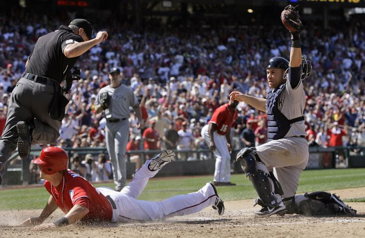 Washington Nationals' Tyler Moore is called out a home on the tag by New York Yankees catcher Russell Martinduring the eighth inning of a baseball game at Nationals Park on Saturday, June 16, 2012 in Washington. The Yankees won 5-3 in 14 innings. (AP Photo/Alex Brandon)