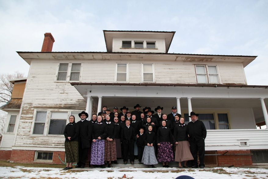 """A Hutterite family is gathered in front of a house in Lewistown, Mont. """"Meet the Hutterites"""" is a National Geographic documentary series about the small religious colony in rural Montana. Three Hutterite bishops have complained the series presents a """"distorted"""" image of the sect. (National Geographic via Associated Press)"""