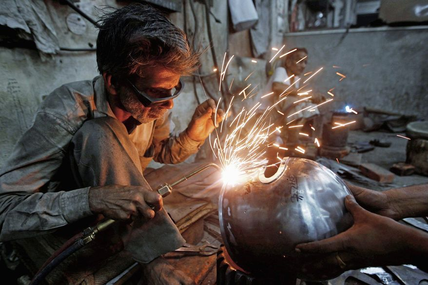 A worker welds a part of a helmet being prepared for a Hollywood period movie. The workshop in Sahibabad, India, fills dozens of orders for all kinds of props for historical movies and documentary films, from Napoleon-era swords to American Revolutionary muskets and sabers to World War II helmets and uniforms. (Associated Press)