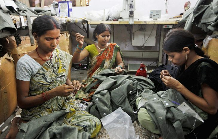 """Workers at Ashok Rai's workshop in India sew military uniforms being prepared for a re-enactment of World War II. """"They have to look authentic,"""" said Mr. Rai. He takes special care to ensure that the replica weapons his workers create are historically accurate. (Associated Press)"""