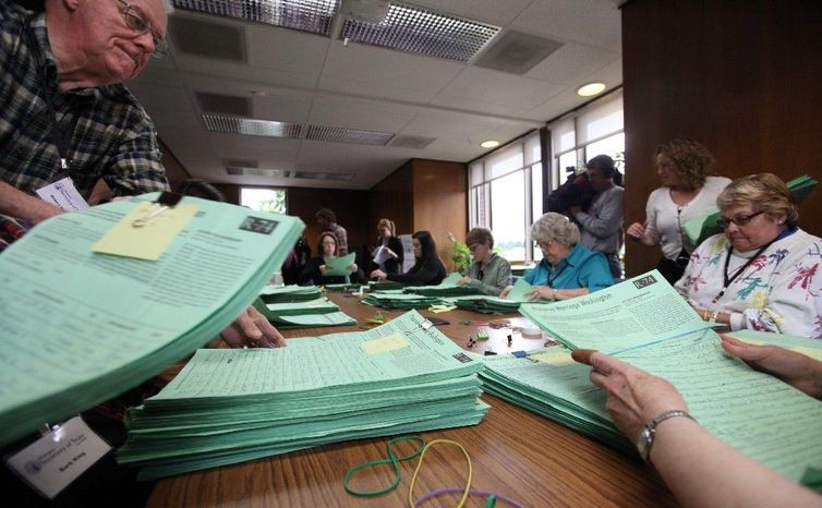 Officials at the Washington Secretary of State's Office in Olympia, Wash., sort petitions June 6 for Referendum 74, which will provide for a public vote in November on whether to overturn a gay-marriage law passed by the Legislature. (Assocaited Press)
