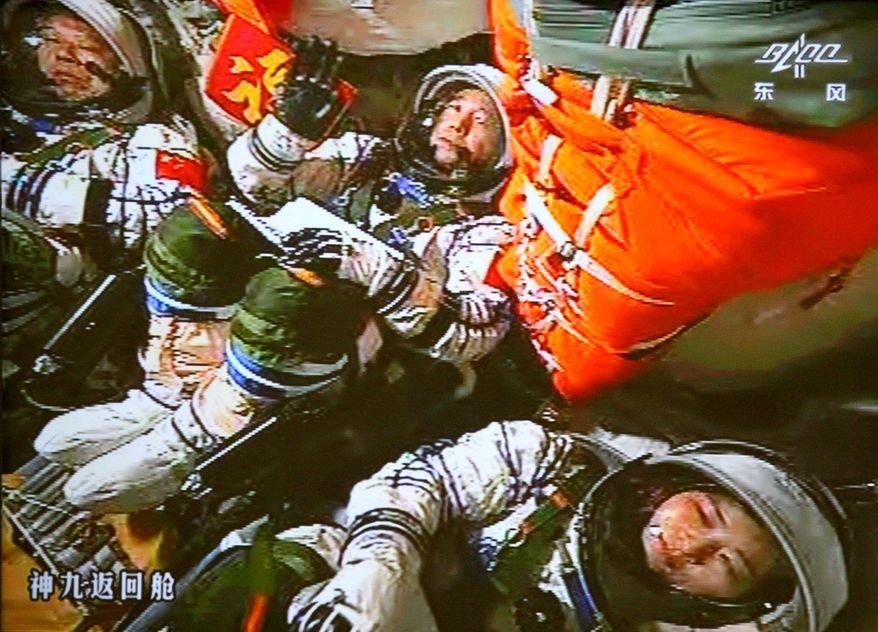 Chinese astronauts Jing Haipeng (center), Liu Wang (left) and Liu Yang sit inside the capsule after the launch of China's manned Shenzhou-9 spacecraft on Saturday, June 16, 2012. Shenzhou-9 blasted off from the Jiuquan Satellite Launch Center in northwestern China. (Associated Press)