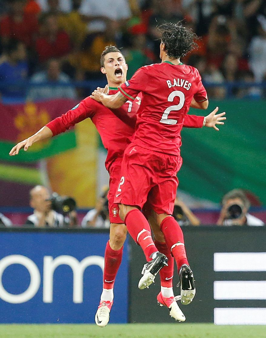 Cristiano Ronaldo ( left) and Bruno Alves celebrate Portugal's second goal during their Euro 2012 Group B match against the Netherlands in Kharkiv, Ukraine. (Associated Press)