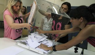 Election officials empty a ballot box to count votes in a parliamentary election at a polling station in Athens on Sunday, June 17, 2012. Greeks voted for the second time in six weeks in what is arguably their country's most critical election in 40 years. (AP Photo/Petros Giannakouris)
