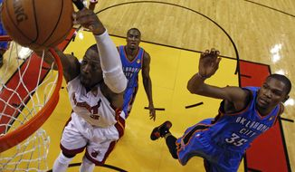 Miami Heat shooting guard Dwyane Wade (3) gets past Oklahoma City Thunder small forward Kevin Durant (35) and power forward Serge Ibaka (9) for a dunk during the second half at Game 3 of the NBA Finals, Sunday, June 17, 2012, in Miami. (AP Photo/Mike Ehrmann, Pool)