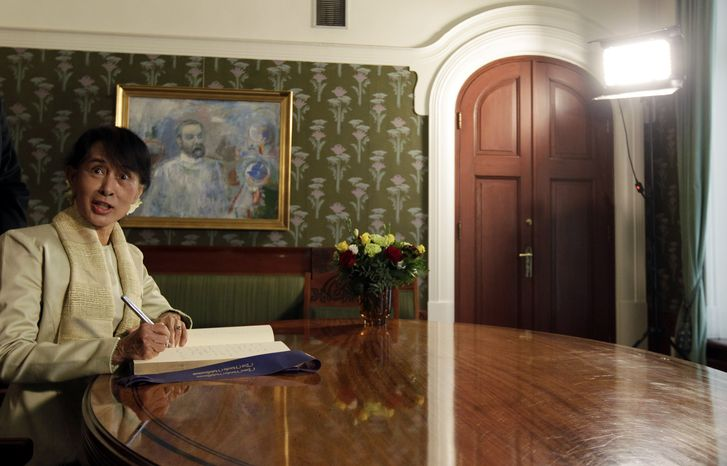 Myanmar opposition leader Aung San Suu Kyi signs a book at the Nobel Institute after a meeting with Norwegian Nobel Committee members in Oslo on Saturday, June 16, 2012. (AP Photo/Cathal McNaughton, Pool)