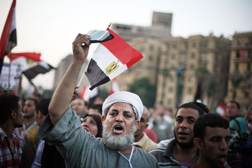 An Egyptian man holds the Quran as he celebrates Islamist candidate Mohammed Morsi's apparent victory in Tahrir Square, Cairo, Egypt, June 18, 2012. Morsi declared victory Monday in Egypt's first free presidential election since Hosni Mubarak's ouster 16 months ago. But just as polls were closing, the ruling military council issued constitutional amendments that gave sweeping authority to maintain its grip on power and subordinate the nominal head of state. (AP Photo/Manu Brabo)