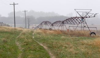 **FILE** An irrigation pivot remains along a highway several miles near the proposed new route for the Keystone XL pipeline in Neligh, Neb. (Associated Press)