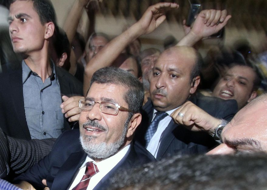 Muslim Brotherhood candidate Mohammed Morsi (foreground) and his supporters celebrate his apparent victory in the Egyptian presidential election at his campaign headquarters in Cairo on Monday, June 18, 2012. (AP Photo/Ahmed Gomaa)