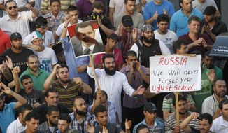 Protesters chant slogans against the Syrian regime and Russia's support of President Bashar Assad, seen in a poster with a shoe on his face, in the southern port city of Sidon, Lebanon, on Sunday, June 17, 2012. (AP Photo/Mohammed Zaatari)