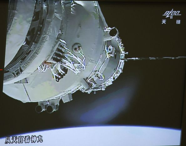 In this image made off the screen at the Beijing Aerospace Control Center and released by China's Xinhua News Agency, China's Shenzhou-9 manned spacecraft (left) docks with the Tiangong-1 space lab module shortly after 2 p.m. Beijing time (2 a.m. EDT) on Monday, June 18, 2012, 213 miles above Earth. (AP Photo/Beijing Aerospace Control Center via Xinhua)