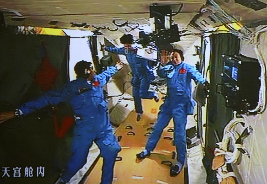 In this image made June 18, 2012, off the monitor screen at the Beijing Aerospace Flight Control Center and released by China's Xinhua News Agency, Chinese astronaut Liu Wang (left) tries to help his female colleague Liu Yang move forward as their commander Jing Haipeng waves in the orbiting Tiangong-1 lab module. They moved from Shenzhou-9 spacecraft to this module three hours after docking earlier that day. (Associated Press/Beijing Aerospace Control Center via Xinhua)