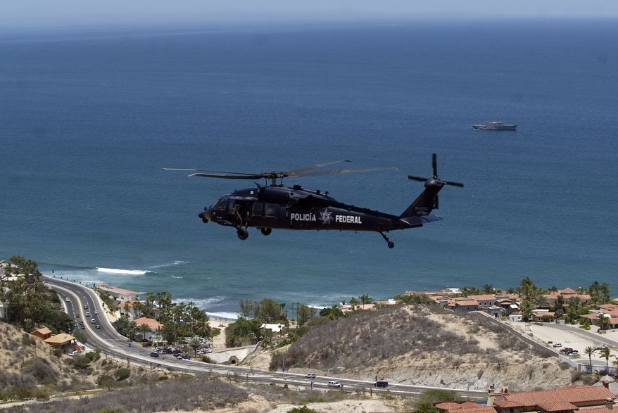 A Mexican federal police helicopter flies June 15, 2012, as a Mexican navy ships patrols the bay waters in San Jose del Cabo in Mexico's Baja Peninsula. Security has been beefed up in preparation for the upcoming G-20 summit that will be held in Los Cabos on June 18 and 19. (Associated Press)