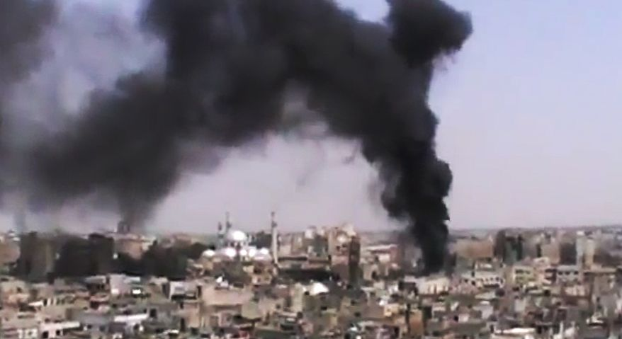 This image made from amateur video, released by the Shaam News Network and accessed on Monday, June 18, 2012, purports to show black smoke rising from buildings in Homs, Syria. (AP Photo/Shaam News Network via AP Video)