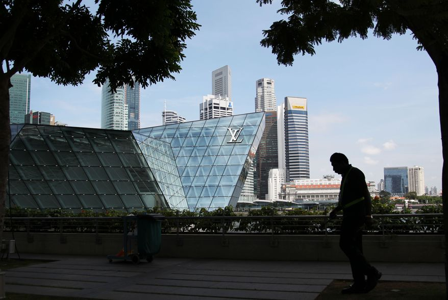 **FILE** A man is silhouetted May 24, 2012, against the skyline of a luxury brand outlet and the financial district of Singapore. (Associated Press)
