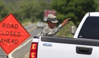 A National Guardsman stops a motorist from driving down Highway 14 north of Laporte, Colo., on Thursday,
