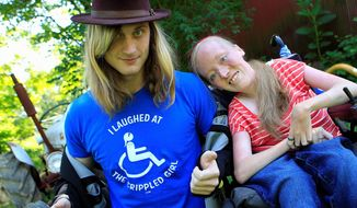 """Ally Bruener, right, poses for a photograph with friend Forest Thomer at her Alexandria, Ky. home on June 13, 2012. Thomer, who says he was charged with disorderly conduct after using the word """"crippled"""" to promote a comedian with muscular dystrophy claims Cincinnati police violated his free speech rights, and the comedian agrees. Thomer, of Cold Spring, Ky., is to appear in a Cincinnati courtroom on the charge Wednesday. He was cited by Cincinnati police last month at a park after he and Bruener say he asked people if they wanted to """"laugh at the crippled girl."""" (AP Photo/The Cincinnati Enquirer, Cara Owsley)"""