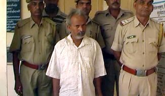 In this image from video footage filmed June 18, 2012, Indian marble miner Oghad Singh (center) stands with policemen after they placed Singh in custody in Charbhuja, Rajasthan state, India. Police said Singh remains unrepentant after beheading his daughter with a ceremonial sword in a rage over her alleged relationships with men. (Associated Press)