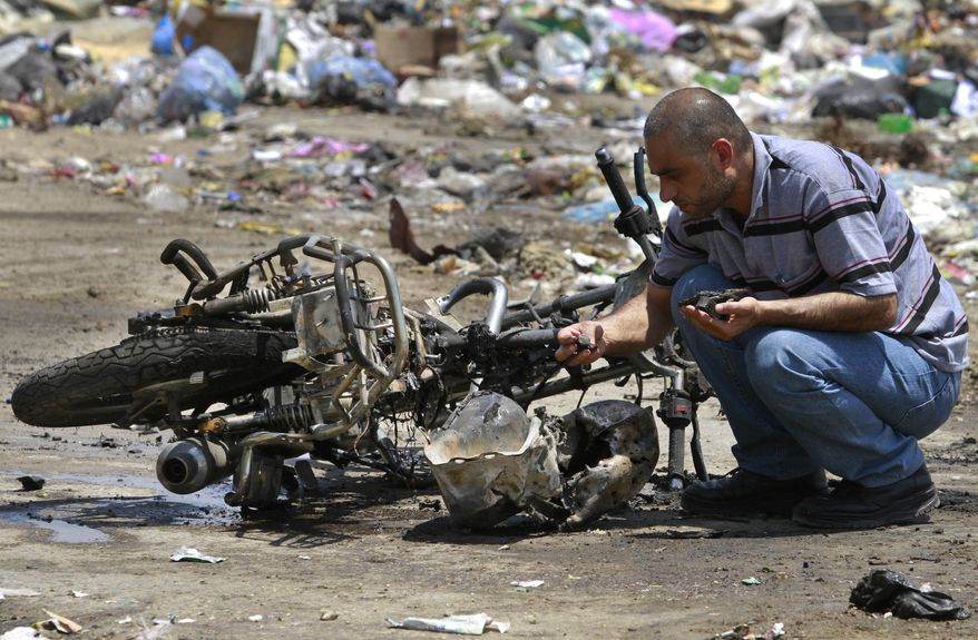 A Palestinian inspects the debris of a destroyed motorcycle on June 18, 2012, after an Israeli airstrike in Beit Hanoun, northern Gaza Strip. (Associated Press)