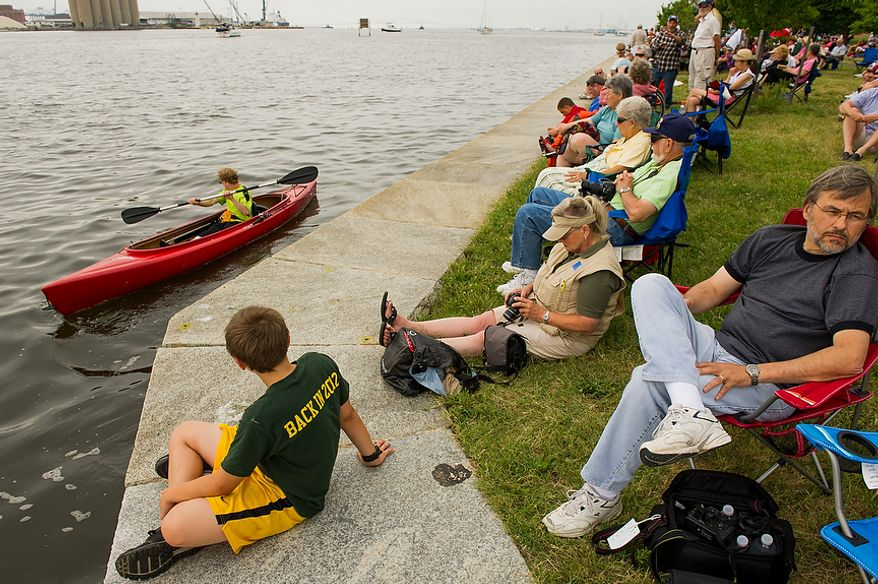 Zachary Doughlas, 10, of Damascus, Md., bottom left, watches James McKnight of Fairfax, Va., left, kyack past visitors to Fort McHenry as they wait to see tall ships depart from Baltimore Harbor after celebrating the Bicentennial of the War of 1812 and the writing of the Star-Spangled Banner as part of a week long international tall ship and naval vessel parade called the Star-Spangled Sailabration, Baltimore, Md., Tuesday, June 19, 2012. (Andrew Harnik/The Washington Times)