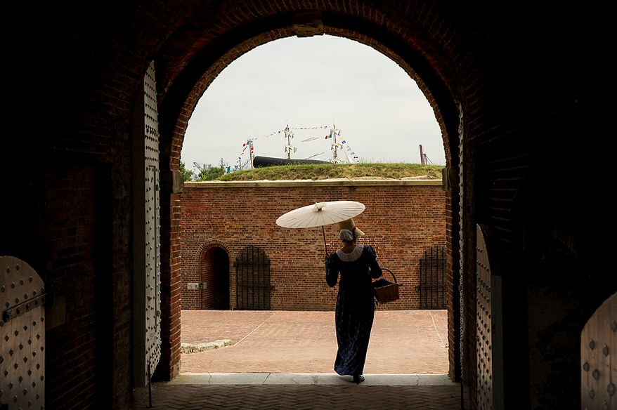 Stephanie Smith, playing a historical citizen of Baltimore walks through the gate of Fort McHenry as the masts of the Cuauhtémoc, a tall ship from Mexico, can be seen in the distance on its way out of Baltimore Harbor after celebrating the Bicentennial of the War of 1812 and the writing of the Star-Spangled Banner as part of a week long international tall ship and naval vessel parade called the Star-Spangled Sailabration, Baltimore, Md., Tuesday, June 19, 2012. (Andrew Harnik/The Washington Times)