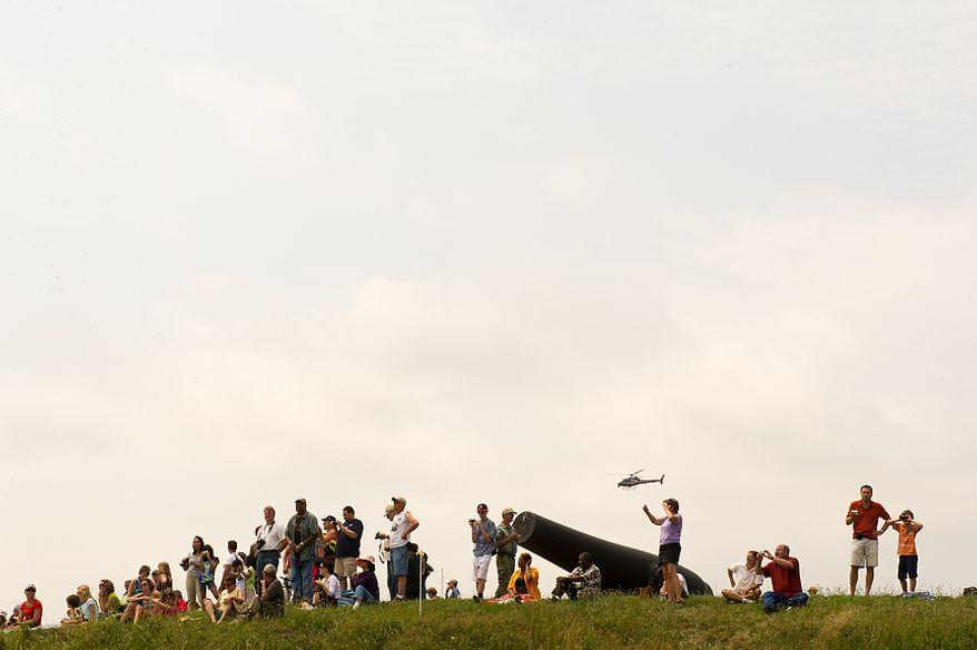 Visitors to Fort McHenry stand on the earthen walls of the fort to watch  tall ships make their out of Baltimore Harbor after celebrating the Bicentennial of the War of 1812 and the writing of the Star-Spangled Banner as part of a week long international tall ship and naval vessel parade called the Star-Spangled Sailabration, Baltimore, Md., Tuesday, June 19, 2012. (Andrew Harnik/The Washington Times)