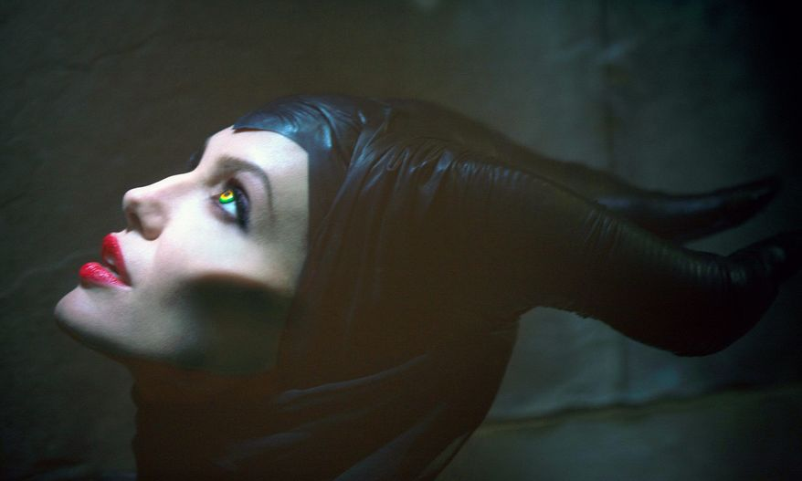 """Actress Angelina Jolie wears a dark headdress and dramatic makeup for the title role as the villain in """"Maleficent."""" (Disney Enterprises Inc. via Associated Press)"""