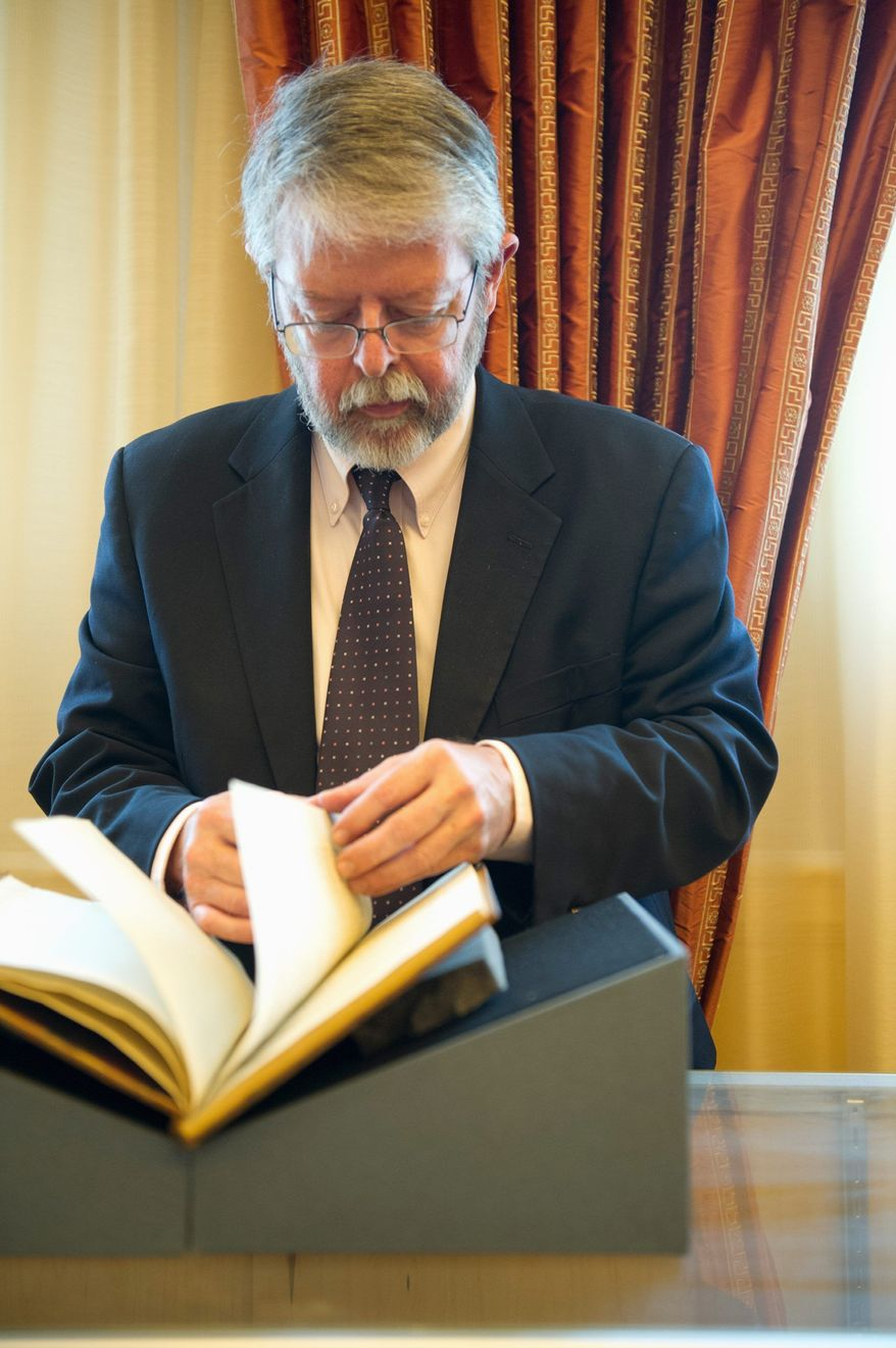 Chris Coover, who specializes in books and manuscripts for Christie's, leafs through George Washington's annotated copy of the Constitution, which is scheduled for auction Friday. (Barbara L. Salisbury/The Washington Times)