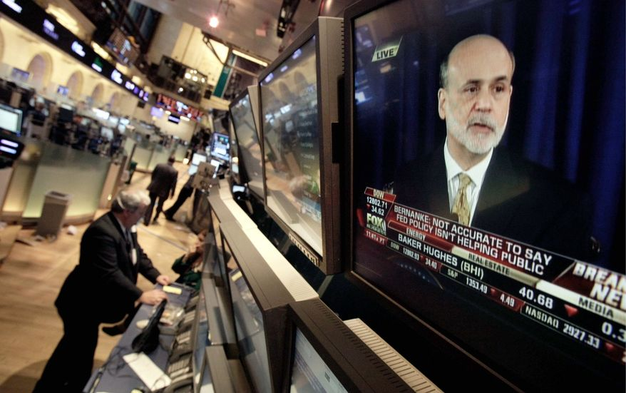 Ben S. Bernanke, chairman of the Fed, appears on a television on the floor of the New York Stock Exchange. Mr. Bernanke said the U.S. economy is being held back by lingering weakness in the housing market. (Associated Press)