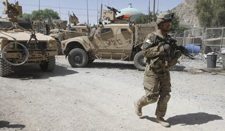 **FILE** A U.S. soldier patrols a police station after it was attacked June 19, 2012, by militants in Kandahar, Afghanistan. (Associated Press)