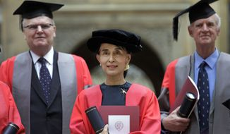 Myanmar opposition leader Aung San Suu Kyi (center) poses for photographers after she accepted an honorary doctorate from England's University of Oxford on Wednesday, June 20, 2012. (AP Photo/Lefteris Pitarakis)