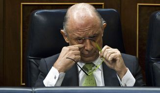 **FILE** Spain's Finance Minister Cristobal Montoro scratches his face June 13, 2012, during a control session at the Spanish Parliament in Madrid. (Associated Press)