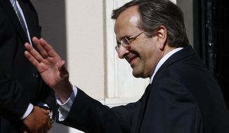 New Greek Prime Minister Antonis Samaras waves after being sworn in on Wednesday, June 20, 2012, in Athens. (AP Photo/Petros Karadjias)