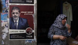 """An Egyptian female vendor stands June 20, 2012, at her shop in Cairo next to a poster with defaced pictures of presidential candidate Mohammed Morsi and Arabic that reads """"Mohammed Morsi, president for Egypt, revival is the will of the people."""" (Associated Press)"""