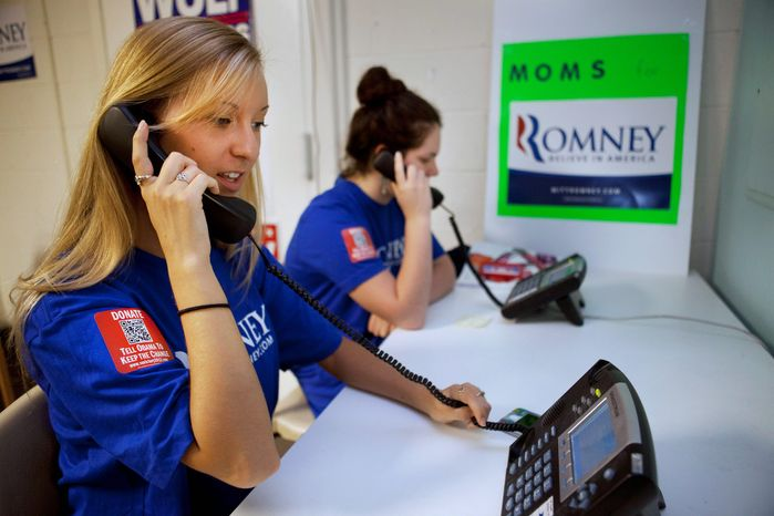 Shannon Westfield, 20, (left) and Jane Kernan, 16, make calls for Mitt Romney in Fairfax wearing T-shirts with a QR code that voters can zap with their smartphones to learn more about the GOP presidential hopeful. In May, Mr. Romney's fundraising almost matched President Obama's, taking in $58 million. (Associated Press)