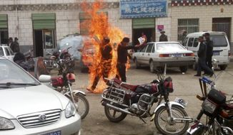In this image made from amateur video footage released by the Tibetan Youth Congress, two Tibetans hold Tibetan independence flags June 20, 2012, as they are engulfed in flames in their self-immolation to protest against Chinese rule, on a street in Yushu prefecture in China's Qinghai province. The group and the official Xinhua News Agency said one of the men died and the other was seriously injured. (Associated Press/The Tibetan Youth Congress)