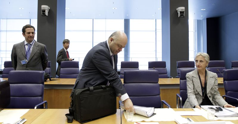 Greek Finance Minister Georgios Zanias (center) removes his papers from his bag during a meeting of eurozone finance ministers in Luxembourg on Thursday, June 21, 2012. (AP Photo/Virginia Mayo)