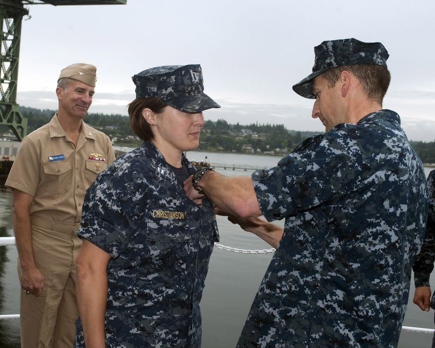 """Lt. Britta Christianson, Gold Crew supply officer for the guided-missile submarine USS Ohio (SSGN 726), is presented with her Submarine Supply Corps """"dolphins"""" by her commanding officer, Capt. Rodney Mills, during a ceremony at Puget Sound Naval Shipyard on June 22. Capt. Dixon Hicks, Ohio's former commanding officer, looks on. Christianson is the first female Supply Corps officer to qualify in submarines. (U.S. Navy photo by Chris Calnan/Released)"""