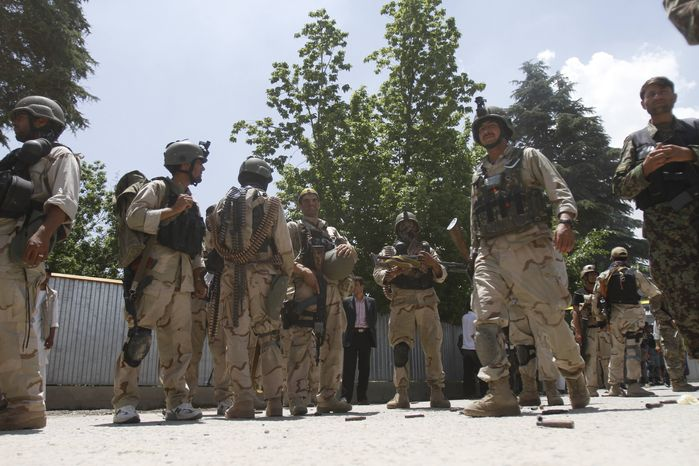 **FILE** Afghan special forces are seen June 22, 2012, outside the Spozhmai hotel at Lake Qargha, just north of Kabul, Afghanistan, where security officials say Taliban insurgents have killed at least 17 people, most of them civilians, in an attack that began before midnight. (Associated Press)