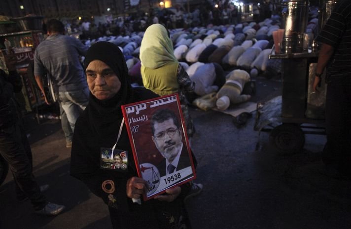 An Egyptian woman holds a banner with the face of Muslim Brotherhood presidential candidate Mohamed Morsi in Cairo's Tahrir Square on June 21, 2012. (Associated Press)