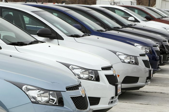 **FILE** A line of 2012 Chevrolet Cruze sedans sits Feb. 19, 2012, at a dealership in the south Denver suburb of Englewood, Colo. (Associated Press)