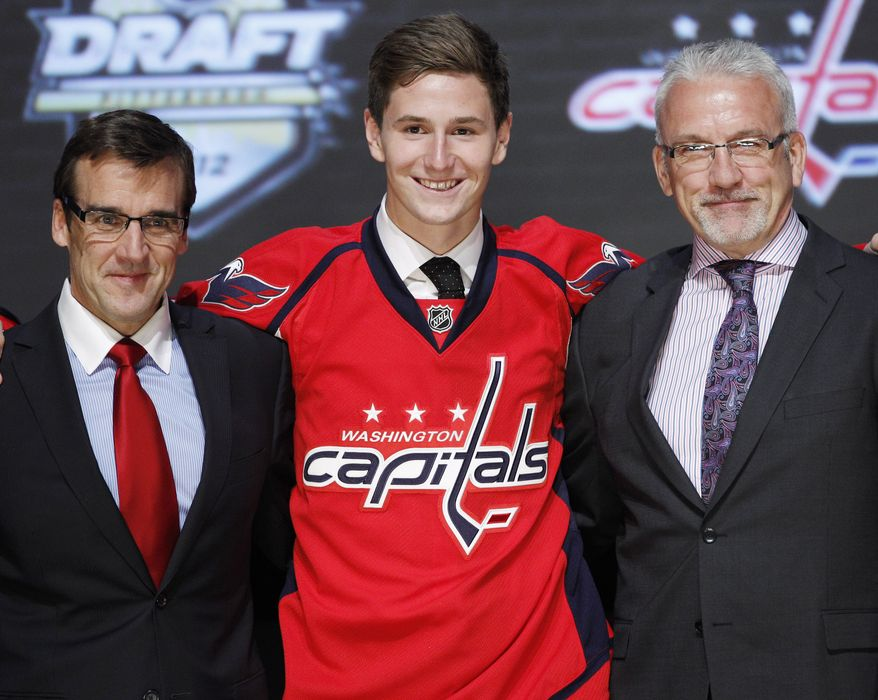 Filip Forsberg, a center from Sweden, smiles with officials from the Washington Capitals after being chosen 11th overall in the first round of the NHL draft Friday, June 22, 2012, in Pittsburgh. (AP Photo/Keith Srakocic)